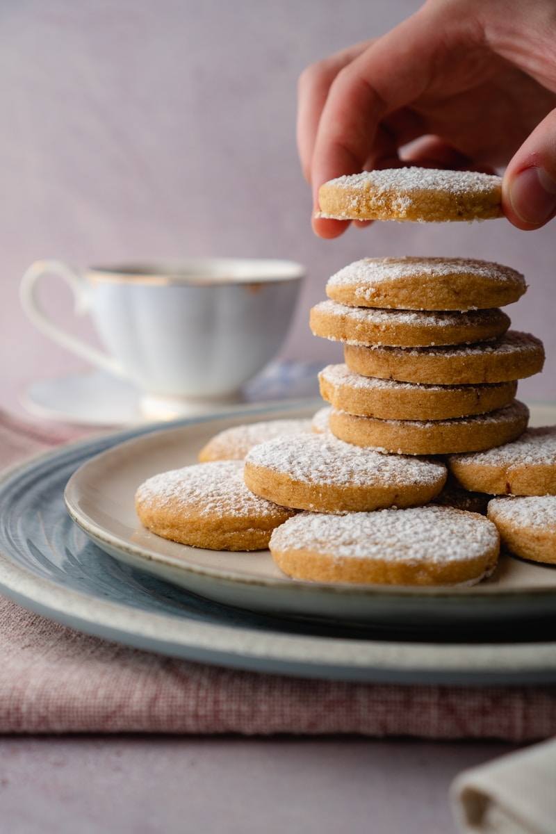 person holding white ceramic mug with brown cookies
